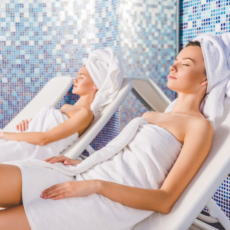attractive young women relaxing on sunbeds at spa center